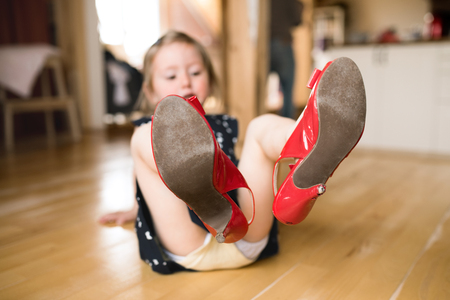 Little girl in dress and red high heels at home.