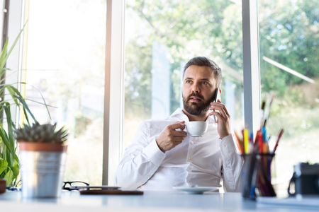 Businessman with smartphone and coffee in his office. photo