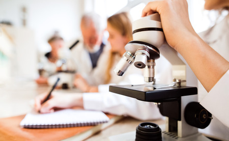 Unrecognizable high school student with microscope in laboratory Stock Photo