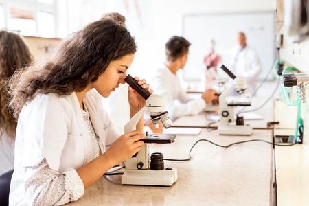 Beautiful high school student with microscope in laboratory. Archivio Fotografico