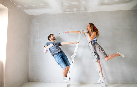 hair roller: Young couple painting walls in their new house. Stock Photo