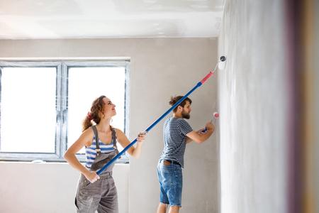 Junges Paar Malerei Wände in ihrem neuen Haus. Standard-Bild - 84759403