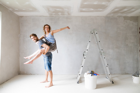 Young couple painting walls in their new house. Stockfoto