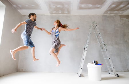Young couple painting walls in their new house. Stock Photo