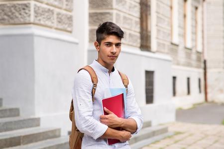 Handsome teenage student in front of old building. Standard-Bild