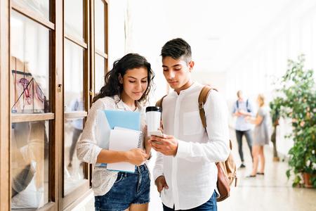 Attractive teenage student couple in high school hall.