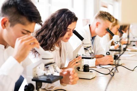 Hermoso estudiantes de secundaria con microscopios en el laboratorio. Foto de archivo - 84829546
