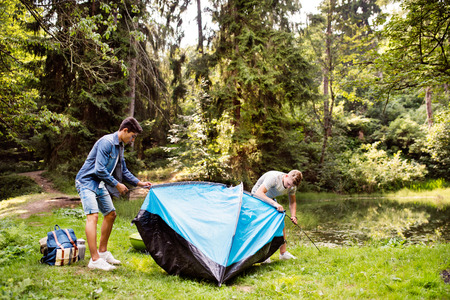 Teenage boys pitching a tent at the lake in forest.