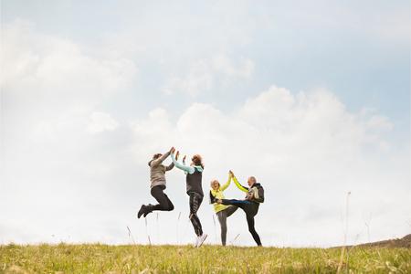 Group of senior runners outdoors, resting, holding hands. 版權商用圖片