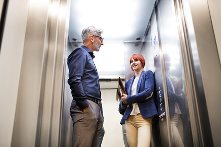 Business people in the elevator in modern office building. Banque d'images