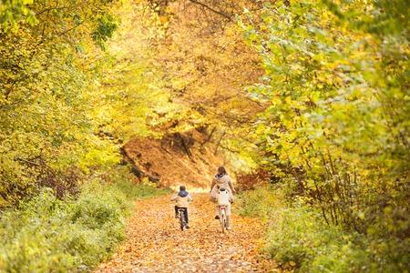 秋の公園でサイクリング小さな息子と母。