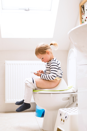 Little girl with smartphone sitting on the toilet.