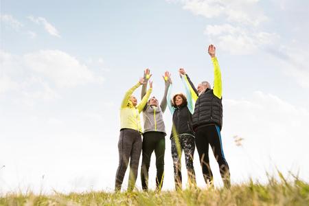 Senior runners outdoors, resting, hands in the air. Reklamní fotografie