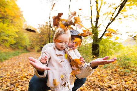 Jonge vader met zijn dochter in de herfstbos.