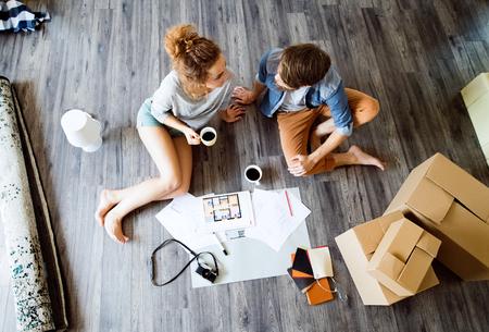 Jong koppel bewegen in een nieuw huis, koffie drinken.