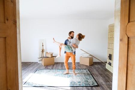 Man met vrouw in zijn armen, verplaatsen in een nieuw huis.