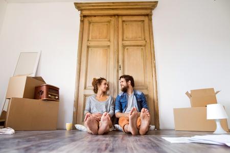 Junge Paare, die im neuen Haus, bewegend sich bewegen.