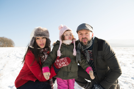 Father and mother with their daughter, winter day. Stock Photo