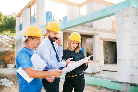 Architetti e lavoratore al cantiere.