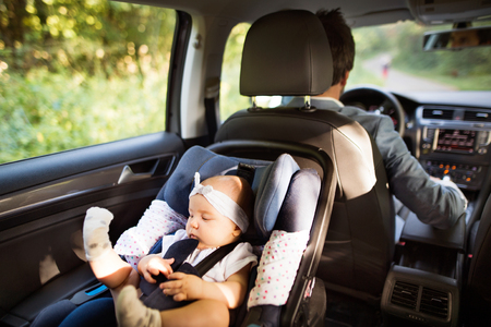 Unrecognizable man driving with a baby girl. Stockfoto