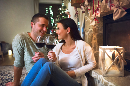 Couple sitting in front of fireplace, drinking wine. Stok Fotoğraf
