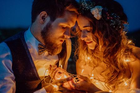 아름 다운 신부 및 신랑은 풀밭에 밤에. 스톡 콘텐츠