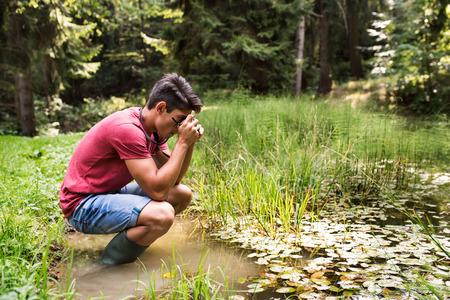 Adolescente com a câmera no lago, tomando a imagem. Foto de archivo - 86900553