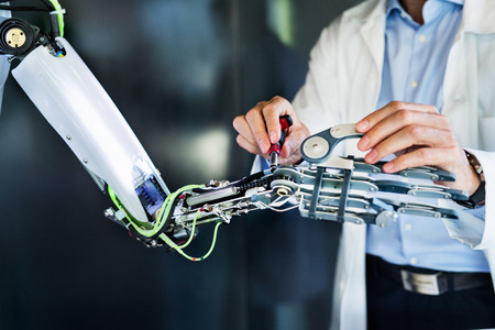 Unrecognizable scientist with a robot. Stock Photo