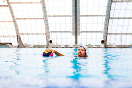 couching: Water polo player in a swimming pool.