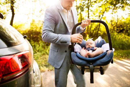 認識できない男は車の座席に彼の女の赤ちゃんを運ぶします。