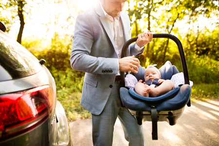 Unrecognizable man carrying his baby girl in a car seat.