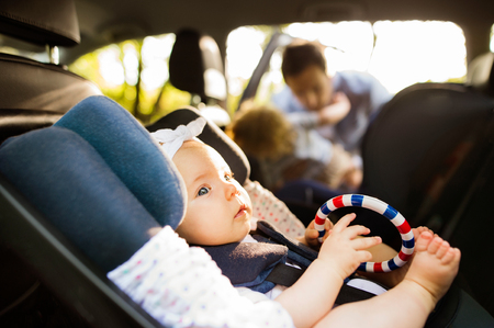 Little baby girl fastened with security belt in safety car seat. Stock Photo