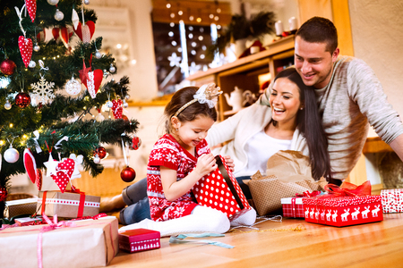 Young family with daughter at Christmas tree at home. Stock Photo - 87265310
