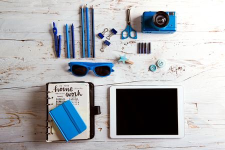 タブレットや学校用品のデスク。白い木製の背景で撮影スタジオ。