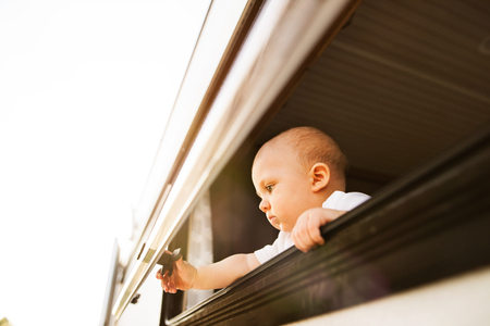 Gorgeous baby boy in a camper van on a summer day. Little boy opening the window.