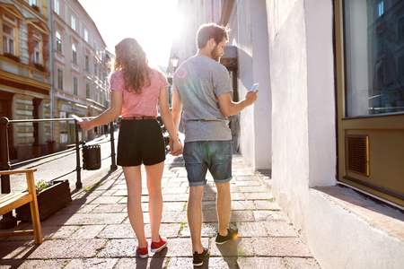 Young couple with smartphones on the street.