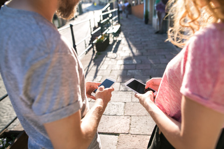 Unrecognizable oung couple with smartphones on the street. Stock Photo