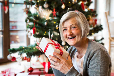 Senior woman in front of Christmas tree with present.