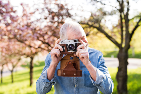 Senior man outside in spring nature taking pictures. Stock Photo
