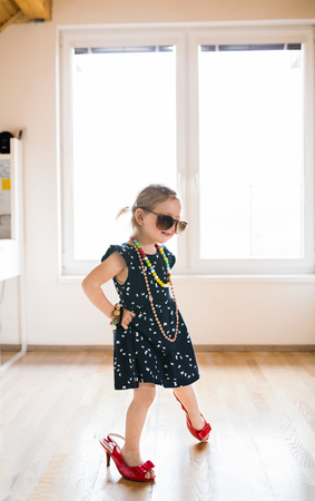Cute little girl in dress and red high heels at home. Фото со стока