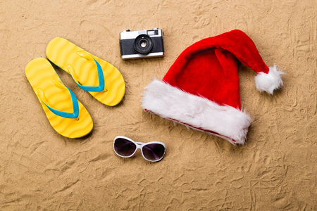 Summer vacation composition with a pair of yellow flip flop sandals, Santa Claus hat, sunglasses and retro styled camera laid on a beach. Sand background, studio shot, flat lay. Stock Photo
