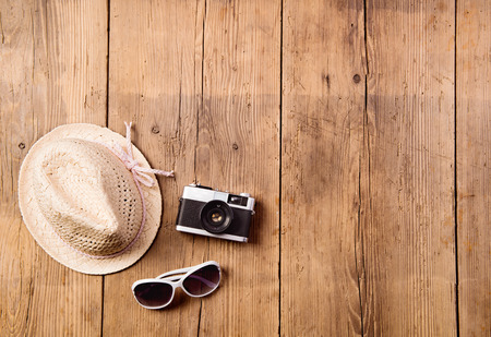 Summer vacation composition. Sunglasses, wicker hat and vintage camera against wooden background. Studio shot, flat lay. Copy space.