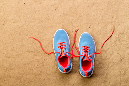 Blue sports shoes with pink shoelaces laid on sand beach background, studio shot, flat lay. Copy space. Stock Photo