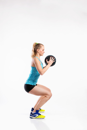 Young fitness woman with medicine ball. Studio shot.