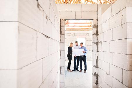 Architecten en burgerlijk ingenieur op de bouwplaats.