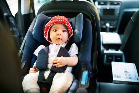 Little baby fastened with security belt in safety car seat. Imagens - 88089675