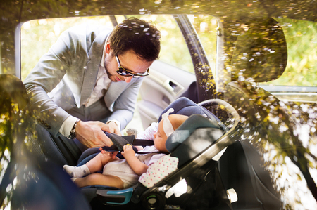 Young father putting baby girl in the car.
