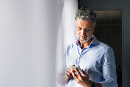Mature businessman with smartphone in a hotel room. Stockfoto