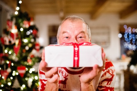 Senior man in front of Christmas tree holding a gift. Stok Fotoğraf - 88089767