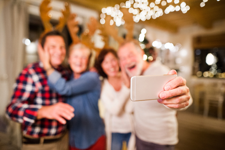 Senior friends with smartphone taking selfie at Christmas time. Stock Photo